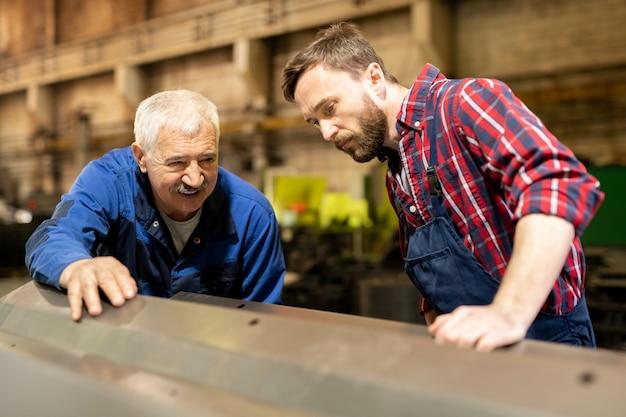 Twee ingenieurs van een grote fabriek buigen zich over een metalen werkstuk en overleggen over de kenmerken ervan
