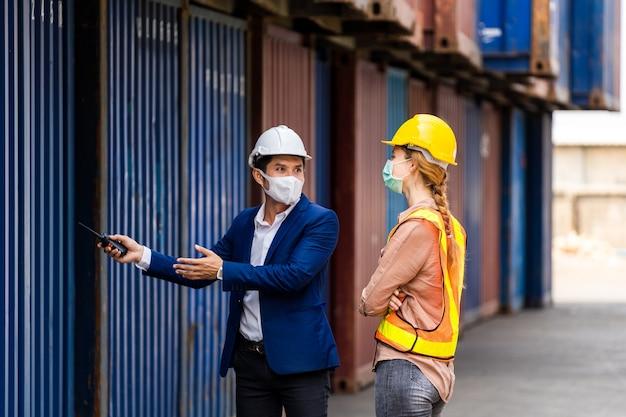 Twee ingenieursarbeiders houden een laptop vast, document voor het controleren van de kwaliteit van de containerdoos van het vrachtschip voor export en import, blauwe containerachtergrond