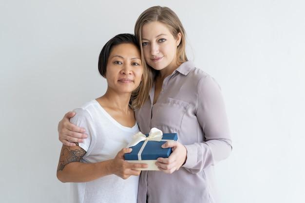 Twee inhoudsvrouwen die giftdoos omhelzen houden