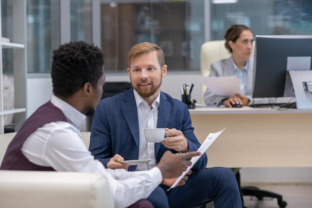 Twee interculturele kantoormedewerkers die papers bespreken