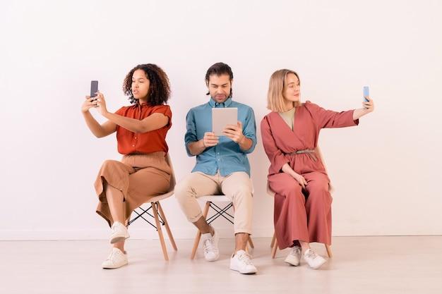 Twee interculturele meisjes met smartphones selfie maken zittend door jonge man met digitale tablet kijken naar online video
