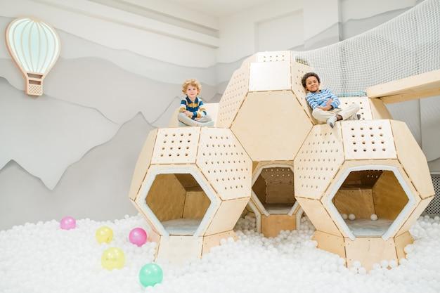 Twee interculturele rustgevende schattige kinderen in vrijetijdskleding zittend op kleine hutten terwijl ze tijd doorbrengen op de speelplaats