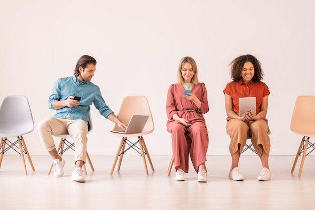 Twee interculturele vrouwelijke millennials zittend op stoelen en met behulp van mobiele gadgets terwijl jonge man met smartphone laptop sleutel duwen