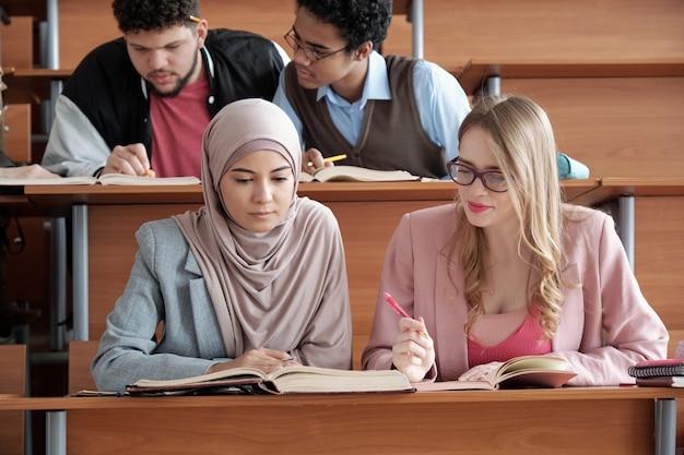 Twee interculturele vrouwelijke studenten van de universiteit zitten aan het bureau in de collegezaal en kijken door de passage in het boek tijdens groepswerk bij les