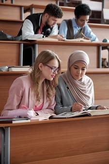 Twee interculturele vrouwelijke studenten van hogeschool of universiteit zitten op de eerste rij bij een bureau in de collegezaal en bespreken de passage in het boek tijdens de les