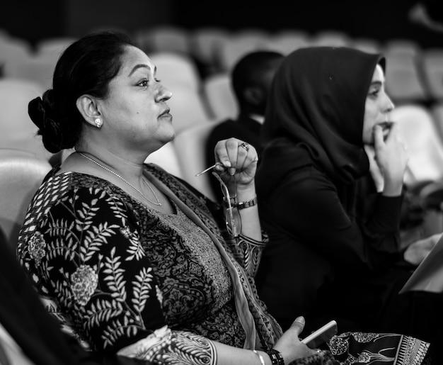 Twee internationale zakenvrouwen zitten in een conferentieruimte