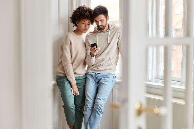 Twee interraciale studenten bekijken aandachtig de instructievideo die wordt gebladerd op een moderne mobiele telefoon, leer cursus online, poseren tegen huiselijk zicht bij raam, verbonden met 4g internet, lezen informatie