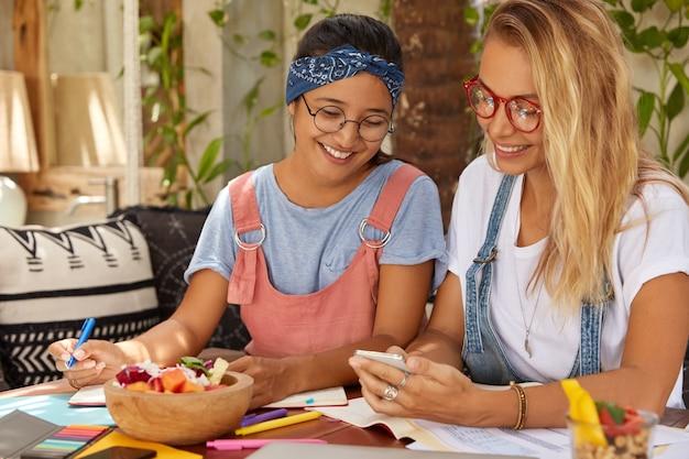 Twee interraciale vriendinnen surfen op internet op hun mobiele telefoon, lezen nieuws Gratis Foto