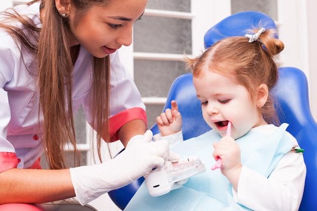 Twee jaar oud meisje leert haar tanden poetsen met een tandenborstel in de hand in de tandartspraktijk