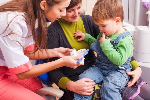 Twee jaar oude jongen met moeder bij het eerste bezoek aan de tandartspraktijk