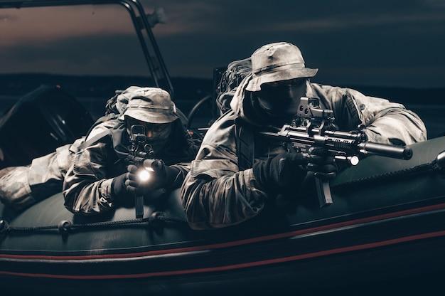 Twee jagers van een speciale eenheid trekken 's nachts door het bos.