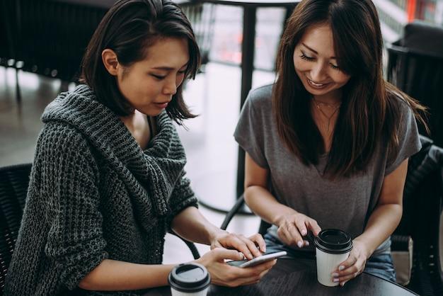 Twee japanse vrouwen rond in tokyo overdag. winkelen en plezier maken