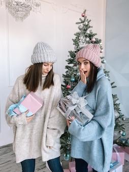 Twee jong meisje truien en hoeden met geschenken dragen