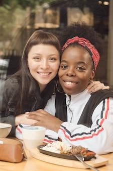 Twee jonge aanhankelijke meisjes kijken je glimlachend aan