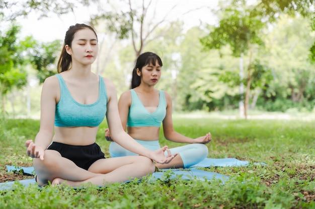 Twee jonge aantrekkelijke atleten aziatische vrouw het praktizeren yoga in de parkaard openlucht op groen gras in de ochtend