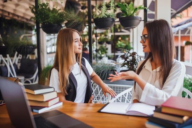 Twee jonge aantrekkelijke bloggers zitten in café en praten