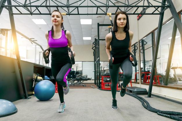 Twee jonge aantrekkelijke fitness vrouwen doen cross fit met riemen systeem