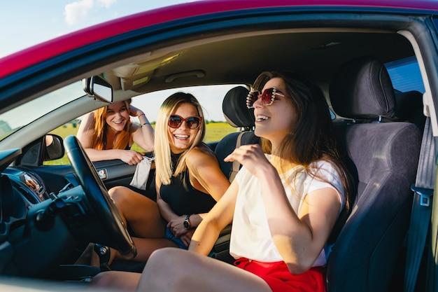 Twee jonge aantrekkelijke meisjes zitten in de autosalon en kletsen met de derde achter het raam, vrouwelijke positieve reisavonturen.