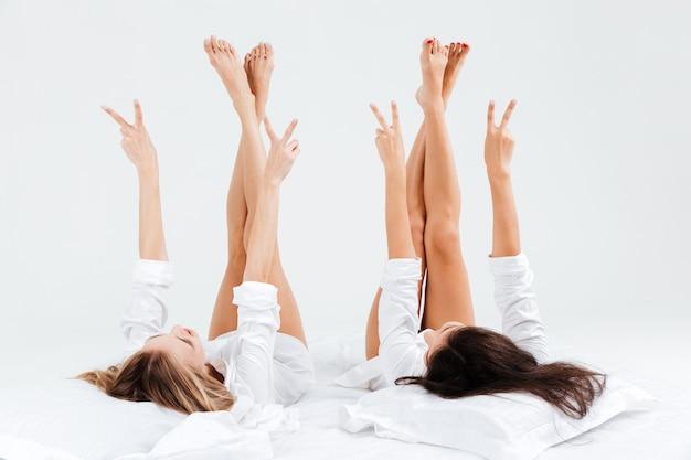 Twee jonge aantrekkelijke vrouwen die overwinningsteken met vingers tonen terwijl ze op bed liggen