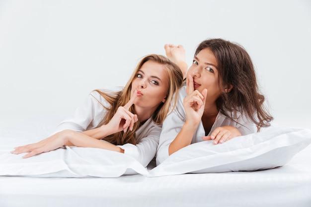 Twee jonge aantrekkelijke vrouwen die stiltegebaar tonen en camera met vinger bekijken