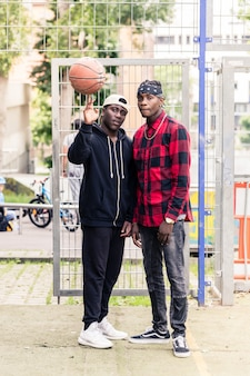 Twee jonge afrikaanse amerikaanse mannen die in openlucht bij het basketbalhof stellen
