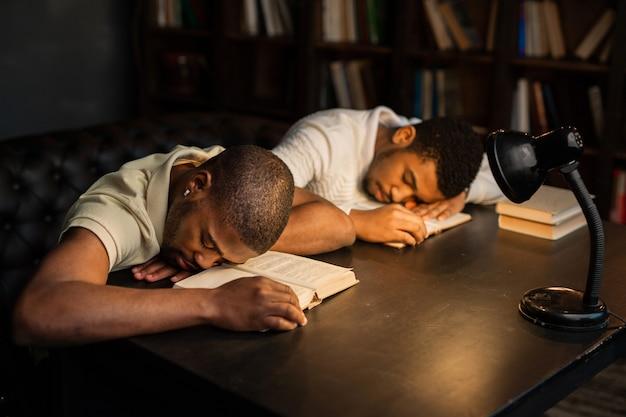 Twee jonge afrikaanse mannen slapen aan een tafel met boeken