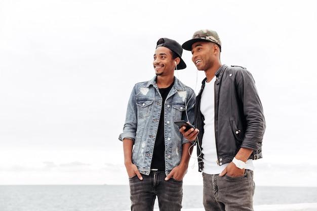 Twee jonge afrikaanse mannen vrienden buiten lopen
