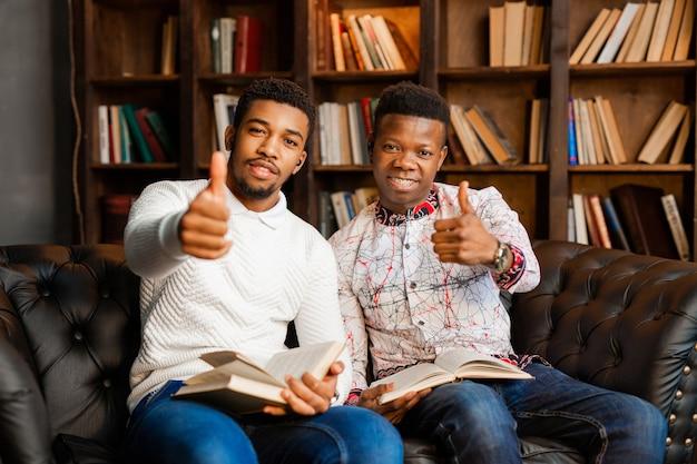 Twee jonge afrikaanse mannen zitten op de bank met boeken met handgebaar