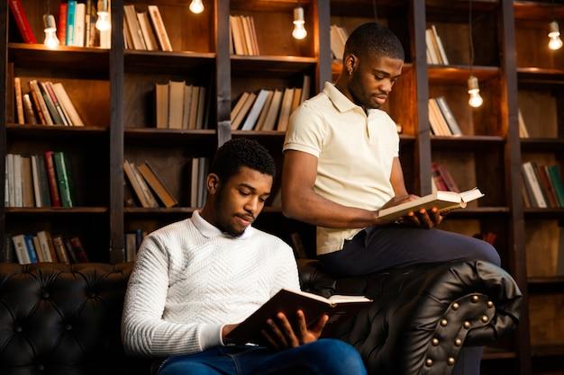 Twee jonge afrikaanse mannen zitten op de bank met boeken
