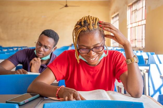 Twee jonge afrikaanse studenten in een klaslokaal, beide met gezichtsmaskers, gelukkig tijdens het studeren