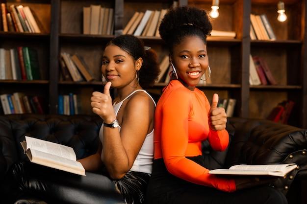 Twee jonge afrikaanse vrouwen die boeken in bibliotheek met handgebaar lezen