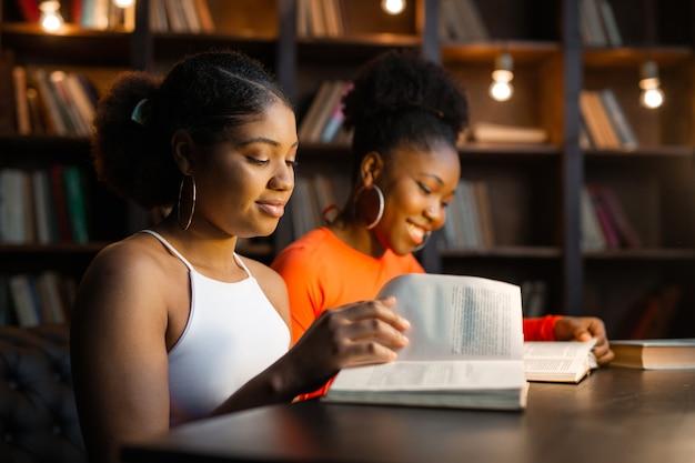 Twee jonge afrikaanse vrouwen die boeken in de bibliotheek lezen