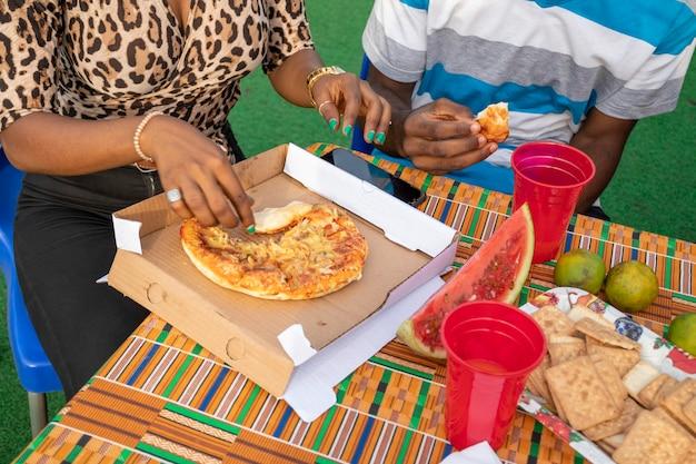 Twee jonge afrikanen die pizza eten