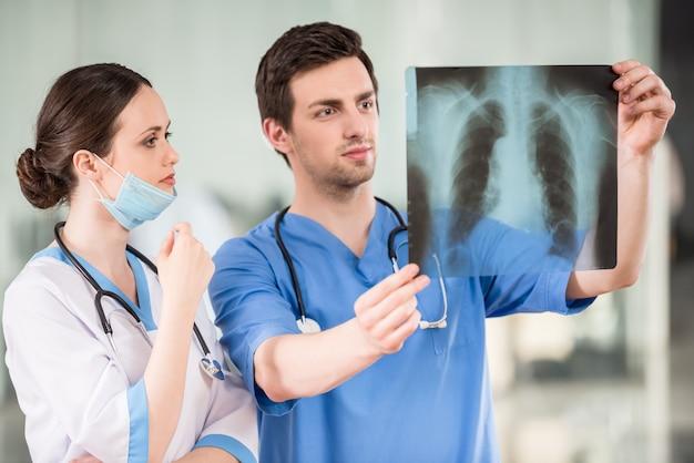 Twee jonge artsen die röntgenfoto op het kantoor van de arts bekijken.