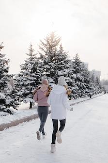 Twee jonge atletische meisjes die in het park op een zonnige winterdag lopen. een gezonde manier van leven.