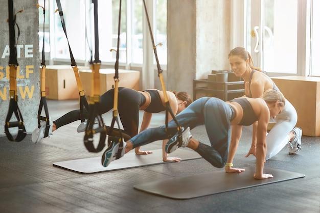 Twee jonge atletische meisjes oefenen met trx fitness bandjes op industriële sportschool met hulp van personal trainer. sport, workout, wellness en een gezonde levensstijl