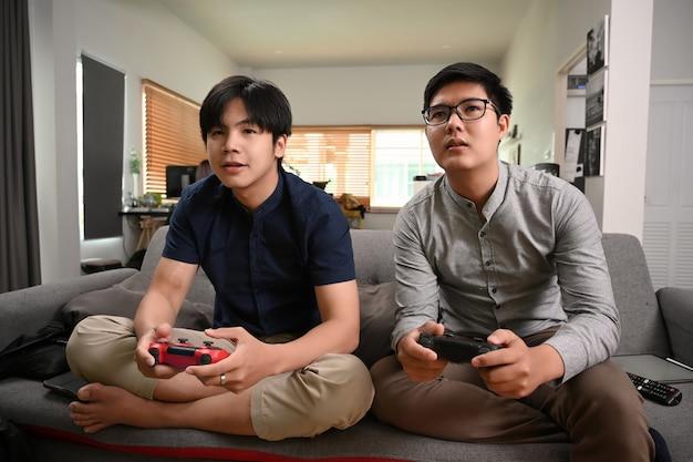 Twee jonge aziatische mannen die videogames spelen terwijl ze thuis op de bank zitten.