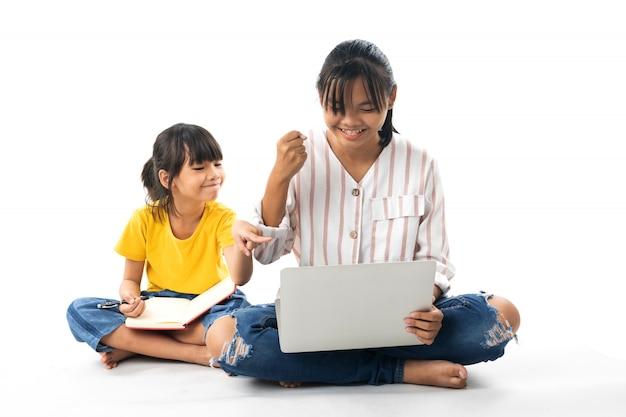 Twee jonge aziatische meisjes die en laptop zitten gebruiken die op witte achtergrond wordt geïsoleerd