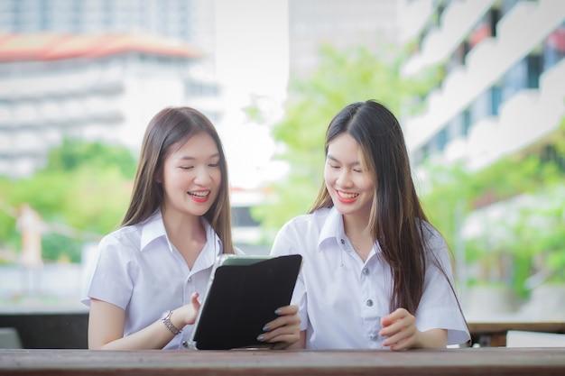 Twee jonge aziatische meisjesstudenten overleggen samen en gebruiken een tablet om informatie te zoeken voor een studierapport.