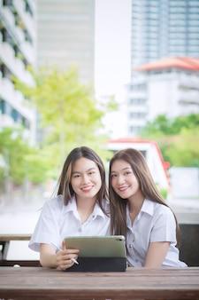 Twee jonge aziatische meisjesstudenten overleggen samen en gebruiken een tablet om informatie te zoeken