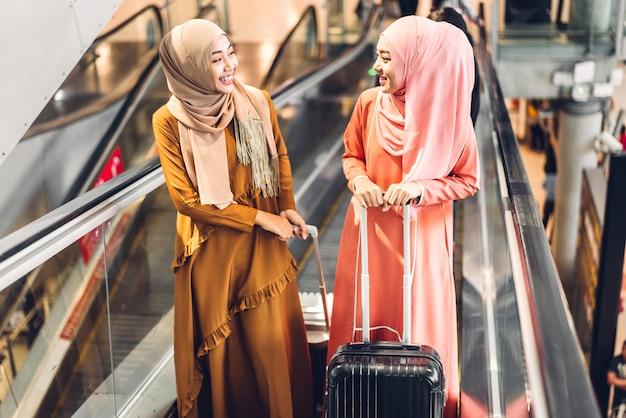 Twee jonge aziatische moslimvrouwen die genieten van winkelen