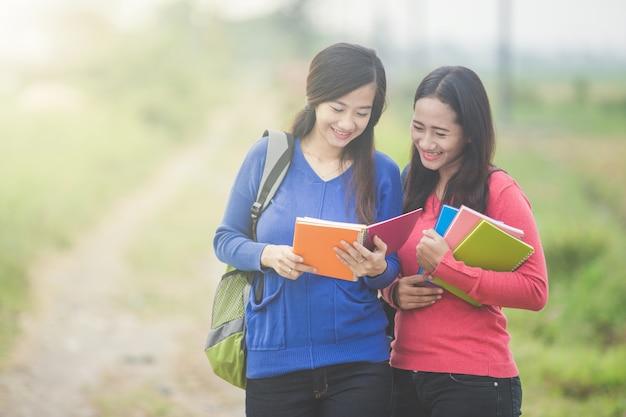 Twee jonge aziatische studenten die iets op het boek lezen