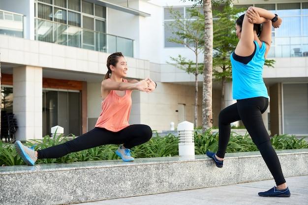 Twee jonge aziatische vrouwelijke joggers die zich in stadsstraat uitrekken