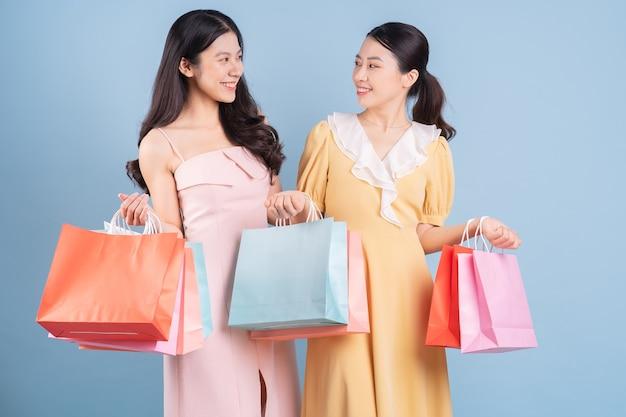 Twee jonge aziatische vrouwen die een boodschappentas op een blauwe achtergrond houden