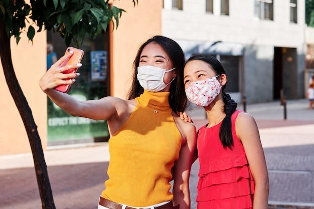 Twee jonge aziatische vrouwen die een selfie met gezichtsmasker