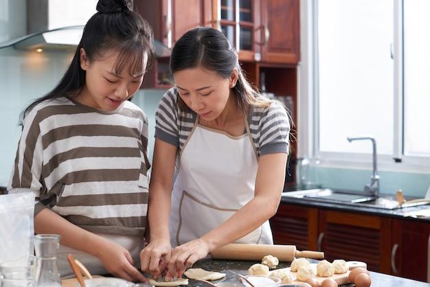 Twee jonge aziatische vrouwen die koekjes van deeg op keukenteller verwijderen