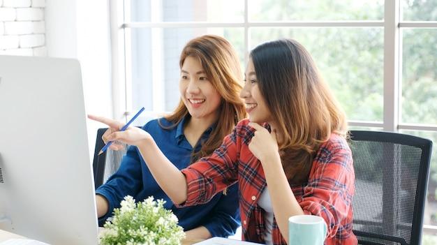 Twee jonge aziatische vrouwen die met computer thuis kantoor werken