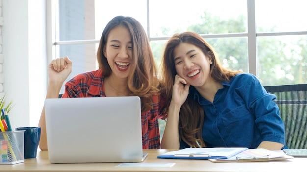 Twee jonge aziatische vrouwen die met laptop computer thuis bureau werken