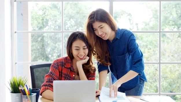 Twee jonge aziatische vrouwen die met laptops werken