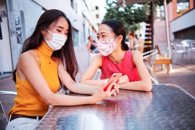 Twee jonge aziatische vrouwen met gezichtsmasker bij bar